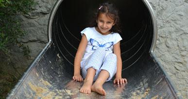 Ab durch die Röhre: Ein Mädchen rutscht auf dem Spielplatz am Weldenbahnradweg. Foto: Kerstin Weidner