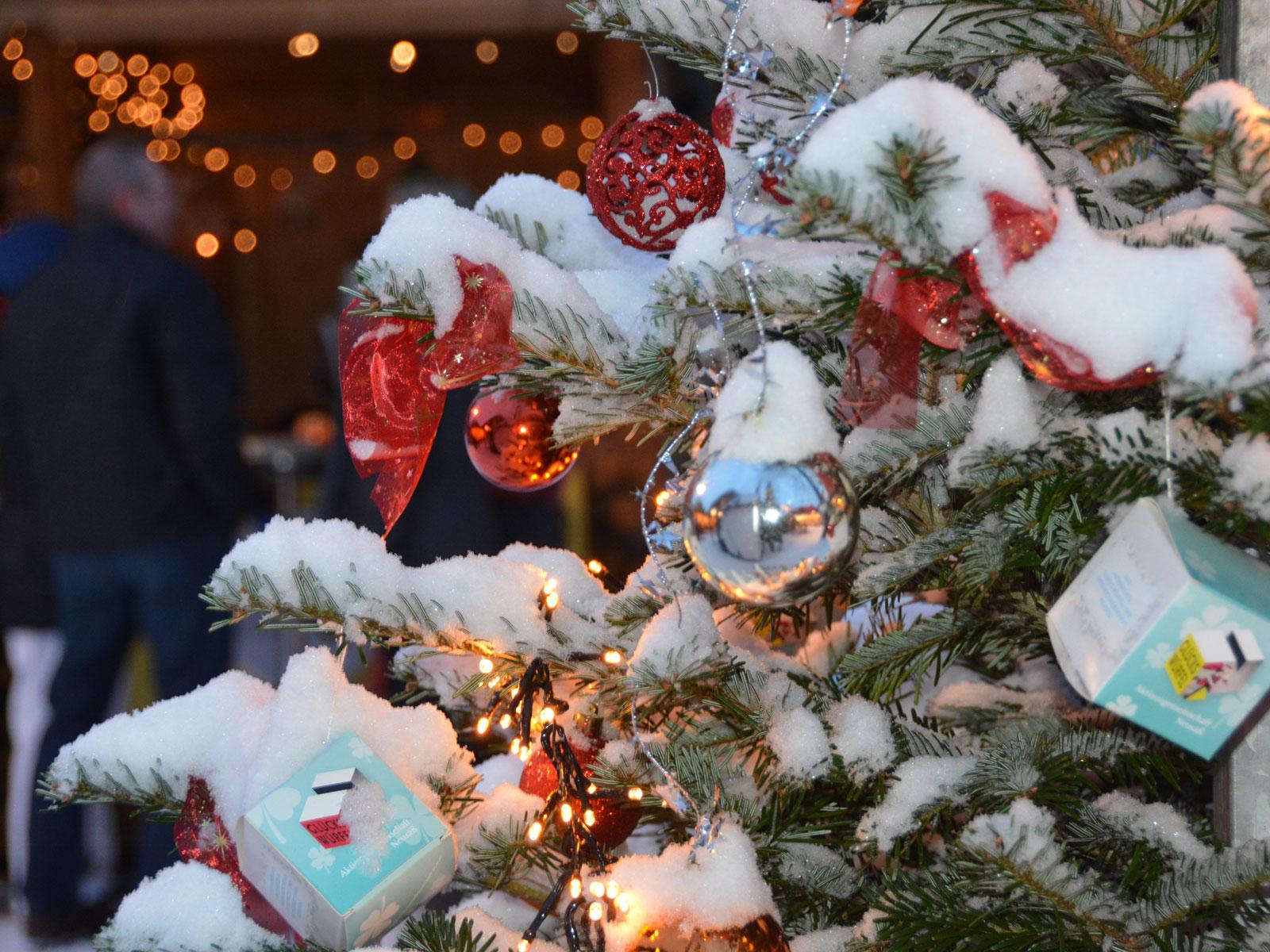 verschneiter Weihnachtsbaum dekoriert mit den Glückswürfeln der Aktionsgemeinschaft Neusäß. Foto: Stadt Neusäß