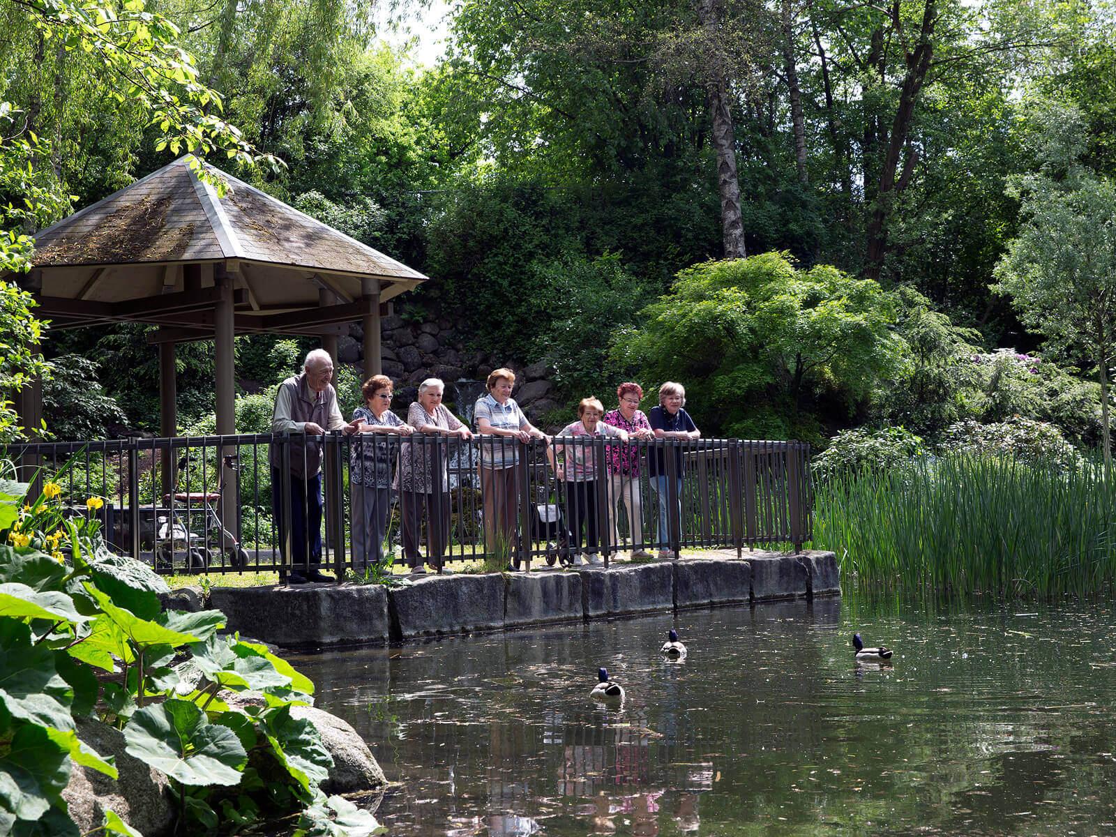 Bewohner des Betreuten Wohnens in der Franzensbader Straße stehen im Pavillon des Schmutterparks und blicken auf den Teich. Foto: Ulrike Klumpp
