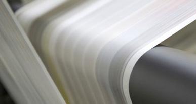 Ein Papierbogen läuft durch eine Druckmaschine. Foto: fotolia.com, Goss Vitalij