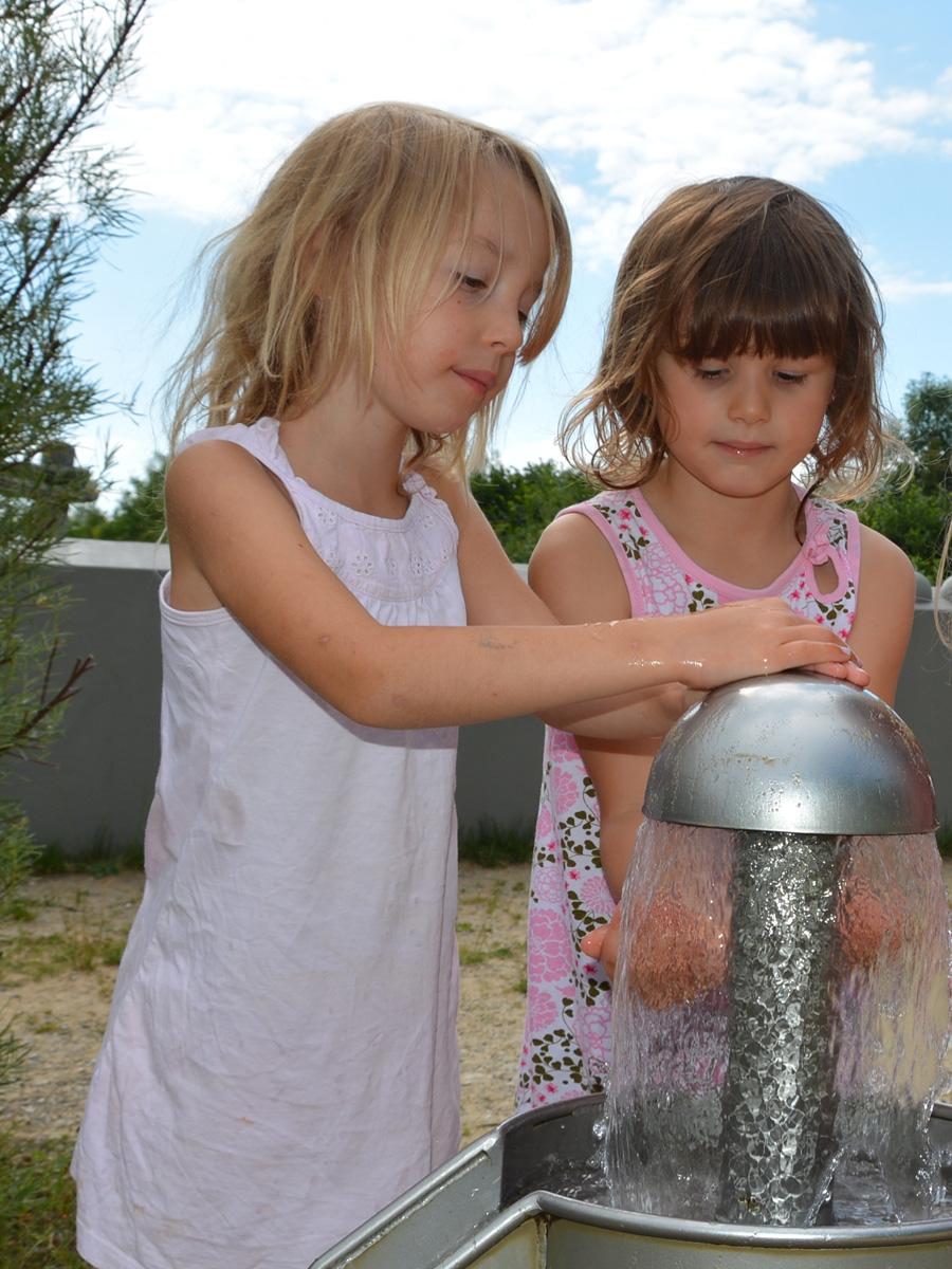 Zwei Kinder testen den Wasserspielplatz