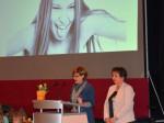 """Organisatorin Maritta Berger (rechts) und Dritte Bürgermeisterin Monika Uhl (links) heißen interessierte Besucherinnen willkommen. Im Hintergrund ein Bild der Fotografin Annabell Fiebiger aus ihrer Ausstellung """"ungeschminkt""""."""