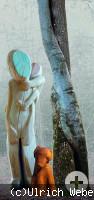 Holzfigur mit Kind und Hund neben Baum