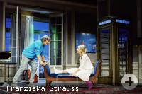 Nora von Collande mit Gipsbein auf dem Sofa, Herbert Hermann diskutiert mit ihr