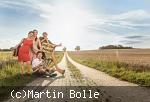 Hans Well mit seinen drei Kindern in Anhalterpose