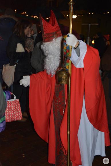 Der Nikolaus verteilt auf dem Weihnachtsmarkt Geschenke an die Kinder.